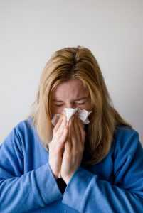 Sick WOMAN sneezing into a tissue